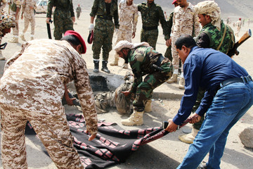 Soldiers carry a dead after a missile attack on a military parade during a graduation ceremony for newly recruited troopers in Aden