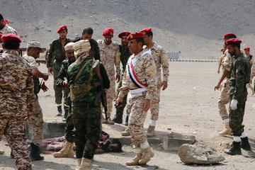 Soldiers gather around a dead body after a missile attack on a military parade during a graduation ceremony for newly recruited troopers in Aden