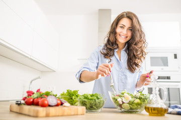 Young woman preparing vegetable salad in her kitchen. Healthy lifestyle concept beautiful woman with mixed vegetable
