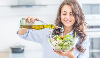 Young woman pouring olive oil in to the salad. Healthy lifestyle eating concept