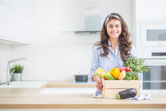 Woman in her kitchen with wooden box full of organic vegetable