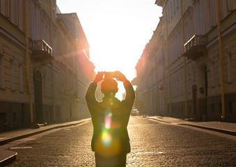 Back view of young man traveller he's a take a picture by smartphone with sunlight on street in Europe