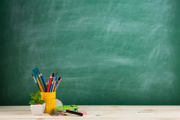 Education concept - school supplies on the desk in the auditorium, blackboard background