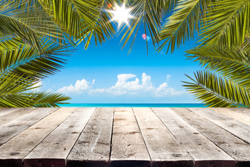 Wooden table background with palm leaves frame and beautiful blue ocean and sky view. Summer sunny...