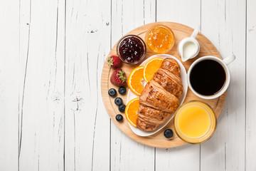 Breakfast with croissants, coffee, orange juice, fruits and berries