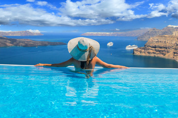 Woman enjoying relaxation in pool and looking at the view