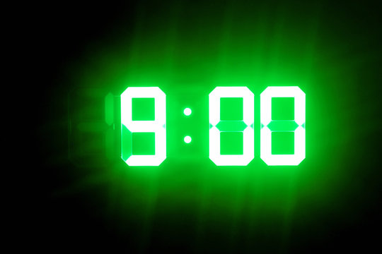 Green glowing digital clocks in the dark show 9:00 time