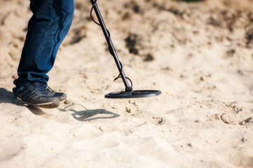 Obraz A man is looking in the sand with a metal detector - fototapety do salonu