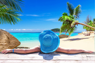 Woman in hat on tropical holidays at the beach