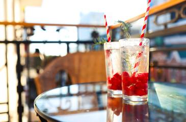 Summer refreshing lemonade with rasberry on a balcony of terrace