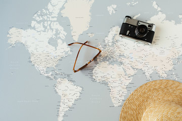 Minimal world map with pins, retro camera, sunglasses, straw hat. Flat lay vacation traveling planning composition. Traveler tourist concept.