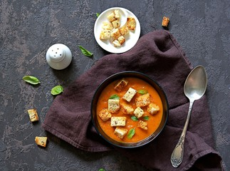 Pumpkin, carrot and tomato puree soup in a black bowl on a dark concrete background. Served with croutons. Thanksgiving day concept. American cuisine. Autumn harvest. Top view