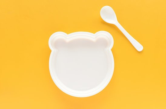 Empty plastic plate with shape of bear and white spoon on yellow background, kids eating, funny food.