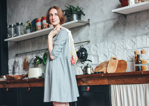 Young woman in grey dress with knitted rag bag string bag shopper in kitchen, zero waste, slow life