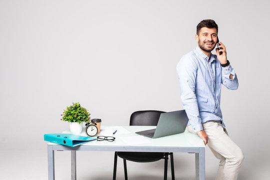 Young businessman speaking on landline phone using laptop