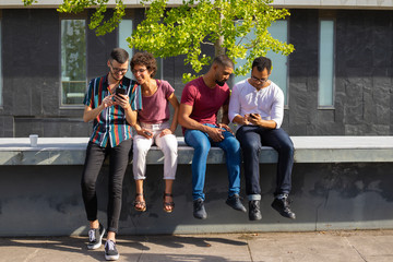 People sitting on parapet outside and watching content on phones together. Men and women using smartphone outdoors. Wireless connection concept