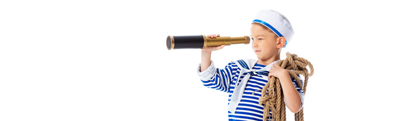 panoramic shot of focused boy in sailor costume holding rope and looking through spyglass isolated on white
