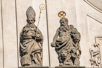 Decorative facade statues of priests and bishops at Saint Salvator church near Charles Bridge in Prague, Czech Republic, summer time, details Wall mural