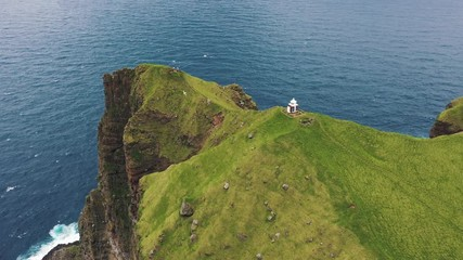 Wall Mural - Flight over a small lighthouse located on a cliff on Kalsoy, Faroe Islands
