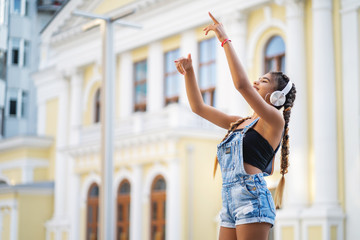 Beautiful mixed race girl listening to music in headphones and dancing. her arms are raised up Fotoväggar