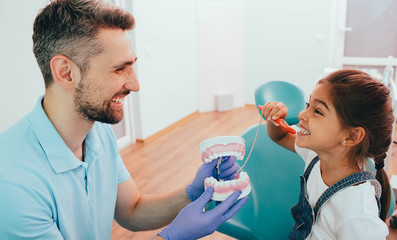 Laughing little girl showing how to brush teeth to her dentist, during a dental appointment