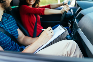 Driving school or test. Beautiful young woman learning how to drive car together with her...