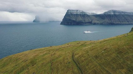 Wall Mural - Flight over mountains on Faroe Islands towards a bay with a cruise ship