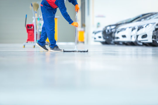 Car mechanic repair service center cleaning using mops to roll water from the epoxy floor. In the car repair service center.