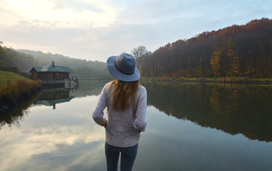 Stylish young woman in a warm sweater and hat, standing on pier by the lake in the park at autumn. Back view.