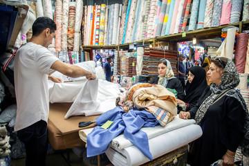 People buy fabric from a store at the Tajrish Bazaar in Tehran