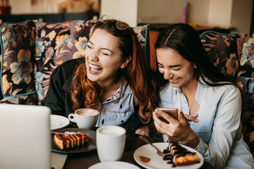 Two girlfriend having fun laughing while sitting in a cafe .