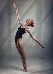 Young and incredibly beautiful ballerina is posing and dancing in a light grey studio full height. The photo greatly reflects the incomparable beauty of a classical ballet art.