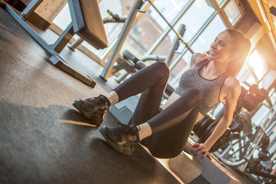 Young fit sporty woman doing triceps dips over stepper platform in gym