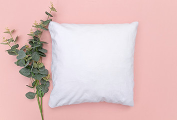 Blank white cushion mock up on pink background with eucalyptus sprig left and space right - empty and ready to add your own design