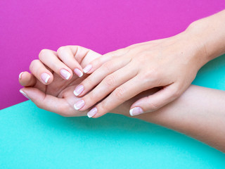 Closeup french manicure in a beauty salon. Woman hand care. Beauty woman nails on a purple and mint pop background
