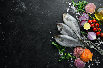 Raw sea fish with lemon, salt and rosemary. On a black background. Top view. Free copy space.