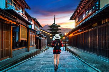 Wall Mural - Woman traveler with backpack walking at Yasaka Pagoda and Sannen Zaka Street in Kyoto, Japan.