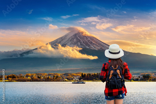 Wall mural Woman traveler with backpack looking to Fuji mountains at sunset in Japan.