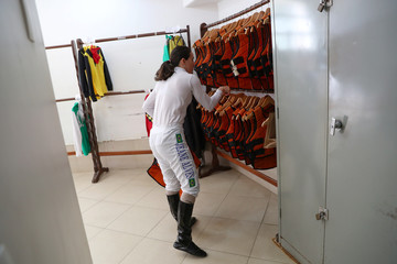 Jeane Alves pics up a horse riding protective equipment as she prepares for a race day at Jockey Club, in Sao Paulo