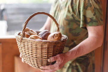 full basket of mushrooms in the hands of an senior man