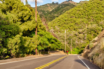 View of Piuma road, a winding highway in Calabasas, southern California, and distant cyclist in red.