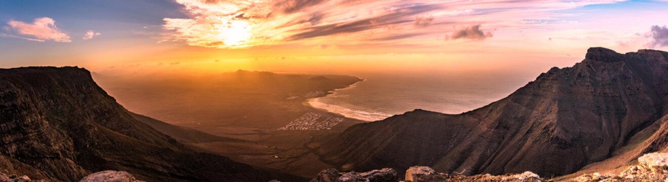 Amazing summer sunset panorama over ocean resort beach Famara Lanzarote Canary Islands, Spain