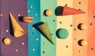 Sweets are scattered on a striped rainbow background: macaroons, waffle horns and small caramels in the shape of stars.