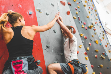 couple of athletes climber moving up on steep rock, climbing on artificial wall indoors. Extreme...
