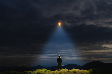 Photo sur Aluminium UFO The UFO shines on a male standing on the mountain