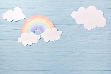 Children or baby background, white clouds with rainbow on the blue wooden background Fototapete