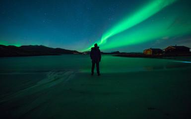 Foto auf Acrylglas Nordlicht Man watching northern light dance in night sky
