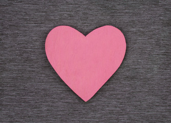 Wooden heart shape, on gray material, as a background texture with design space.