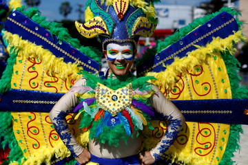 A performer poses for a picture as he waits for the opening parade of the festivities of El Divino Salvador del Mundo (The Divine Savior of The World), patron saint of the capital city of San Salvador