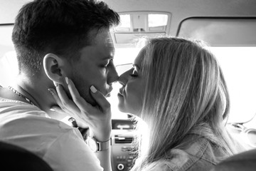 Couple in love man and woman kissing sitting in the car